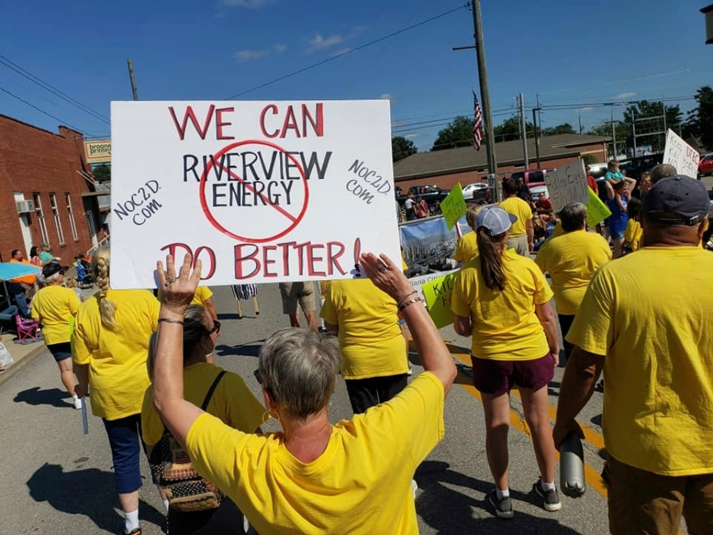 "Protestors in yellow shirts holding a sign saying ""We can do better"" with ""Riverview EnergyEnergy"" having a red circle and slash around it and ""NOC2D.com"" written on the sides"